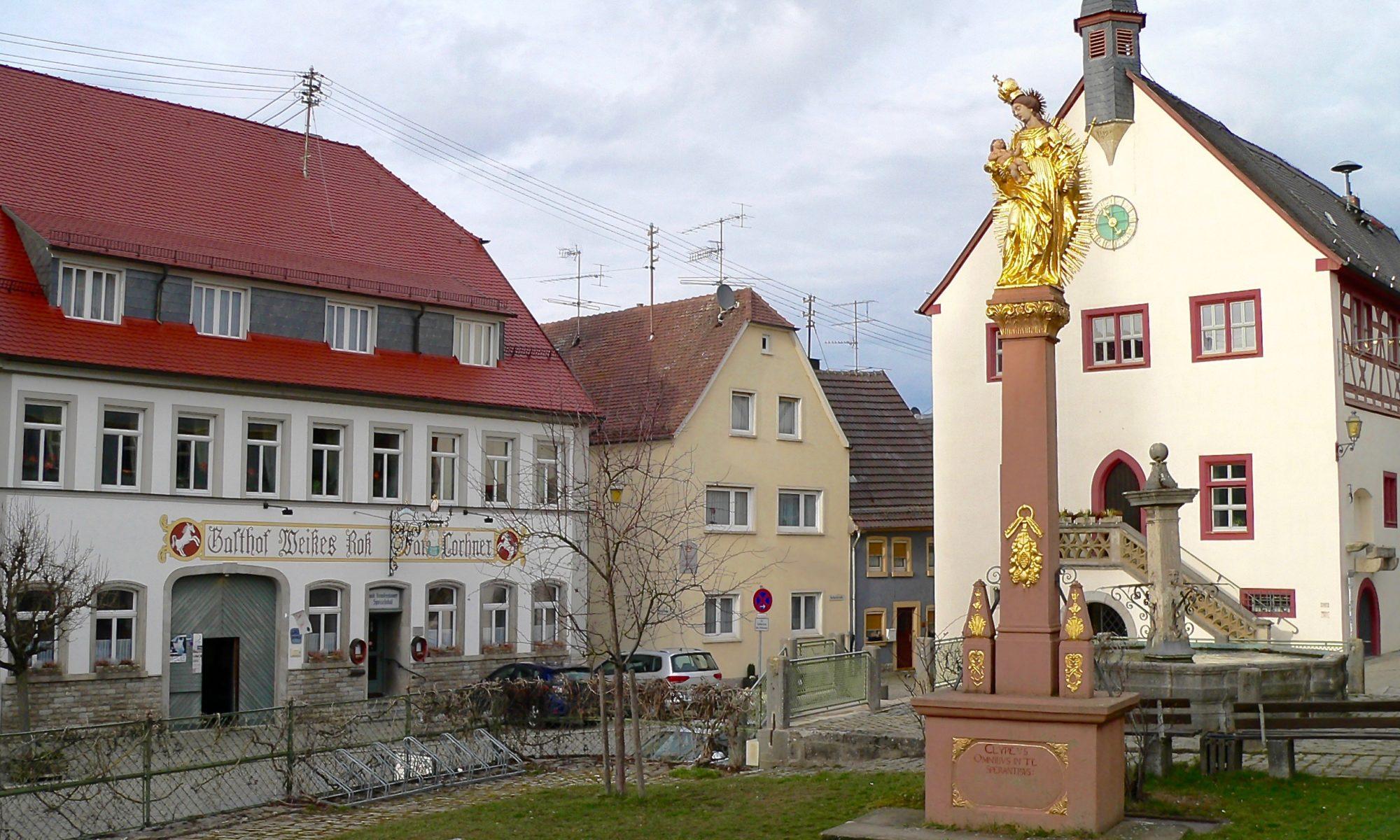 Golden glänzt die Mariensäule von 1722 vor dem historischem Rathaus, dem Sitz der Verwaltungsmeinschaft Aub. Früher fanden auf dem Platz vier Märkte im Jahr statt. Aktuell werden ein Frühlings-, ein Kirchweih- und ein Weihnachtsmarkt veranstaltet. | Foto: B. Schneider