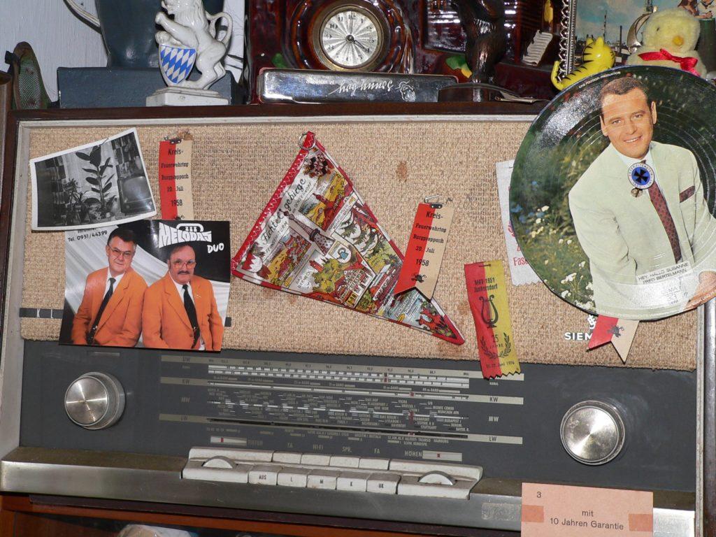 Ja, so war das. Ehrennadeln, Sportabzeichen der Kinder und Eintrittsfähnchen von Jubiläumsfesten steckte man früher gerne an den Stoffvorhang des Radioapparats.