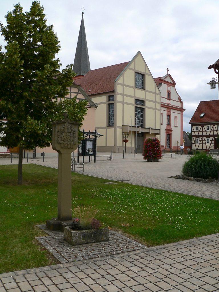 Die beiden Giebel der Pfarrkirche St. Johannes der Täufer säumen in Stadtlauringen die obere Seite des Marktplatzes, die des Rathauses die untere.