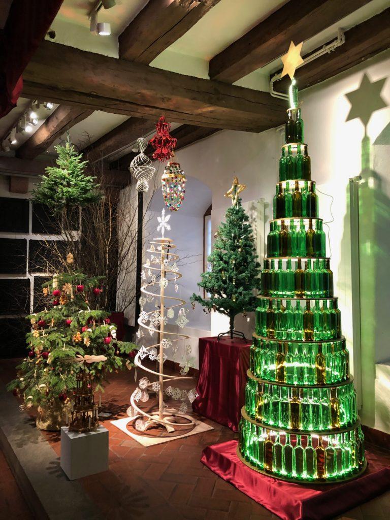 """Christbäume in unterschiedlichen Stilen: klassisch als dekorierter Nadelbaum, zeitlos aus der """"Oskar-Designmanufaktur"""" in Lohr a. Main als Spiralbaum aus verleimten Furnierholz und modern als von innen heraus beleuchteter Glasbaum aus Weinflaschen."""