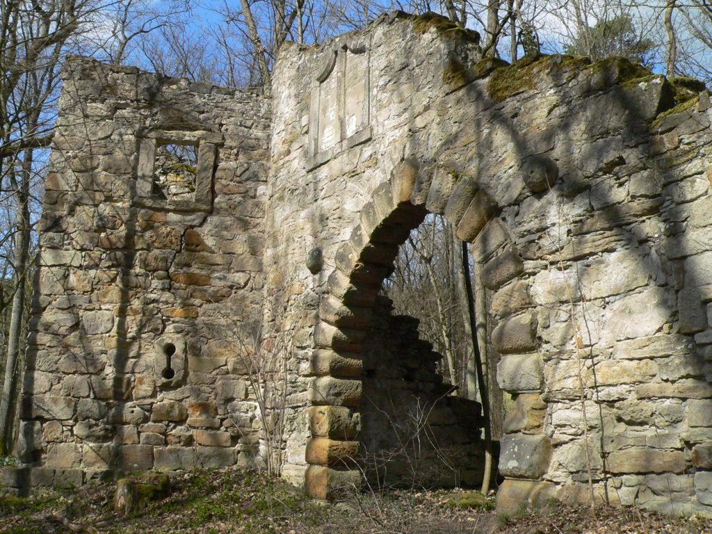 """Die """"Alte Burg"""" ist eine künstlich geschaffene Ruine. Um die historische Verbindung zur Bettenburg herzustellen, wurde über dem Torbogen das hennebergische Wappen, der Hahn, angebracht. Außerdem ist im Gemäuer eine burgenkundliche Besonderheit zu finden: eine Brillenscharte."""